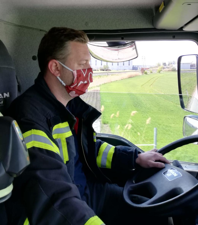 Feuerwehrmann fährt mit Schutzmaske